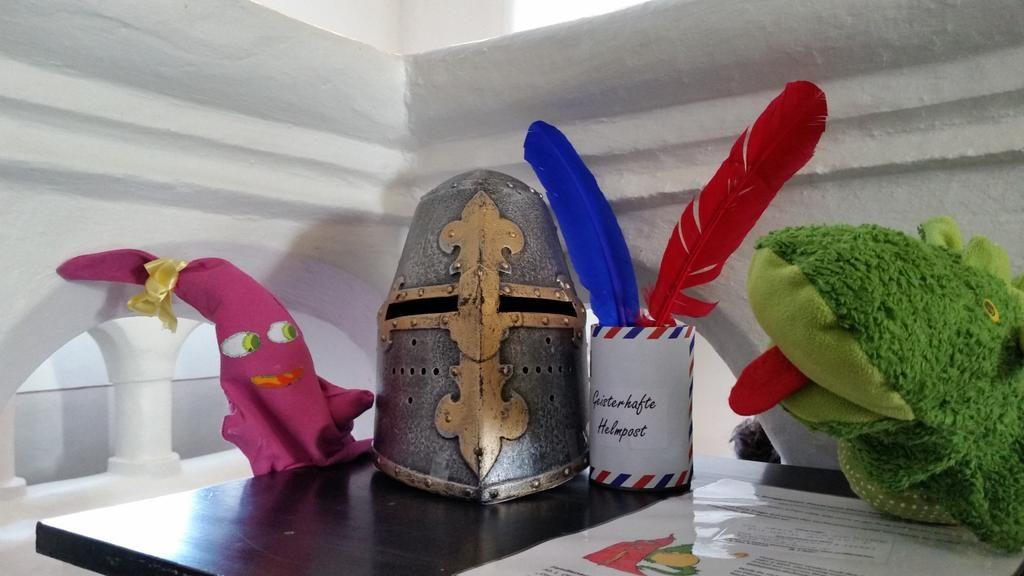 """Die Burggeister Posti und Stein posieren mit der """"Helm-Post"""" in der Halle der Burg. Dort können Fragen eingeworfen werden."""