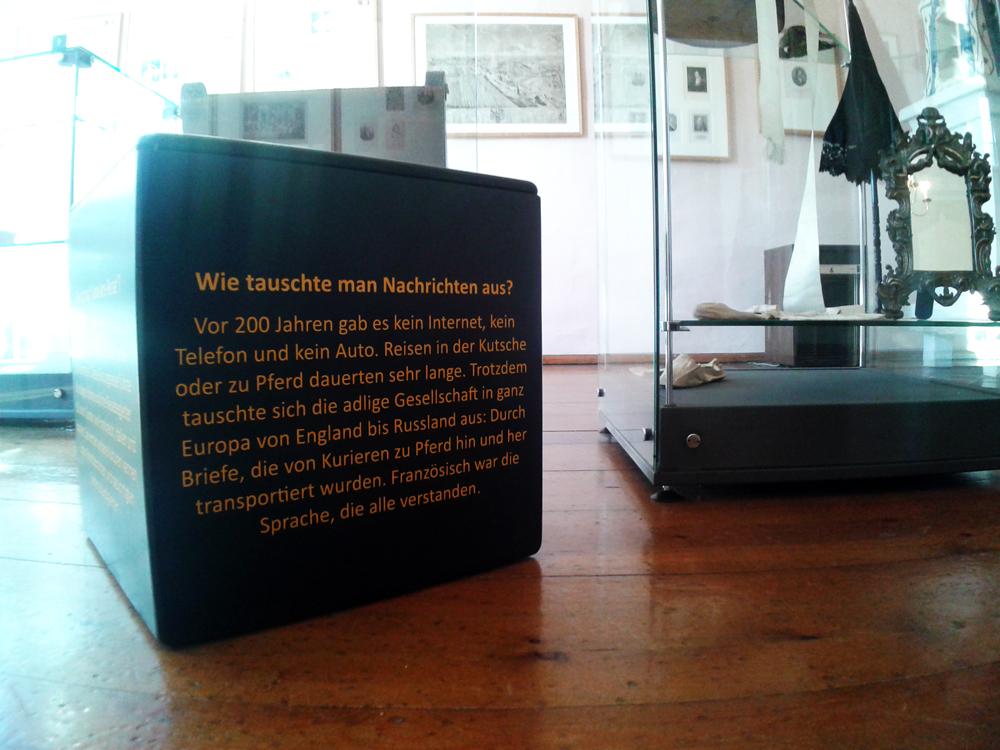 Schwarze Würfel in der Ausstellung dienen nicht nur als Sitzgelegenheit, sondern beantworten auch Kinderfragen in einfachen Sätzen.