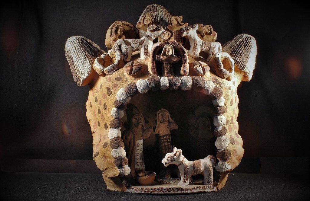 Weihnachtskrippe aus Peru, die von drei Hunden bewacht wird.