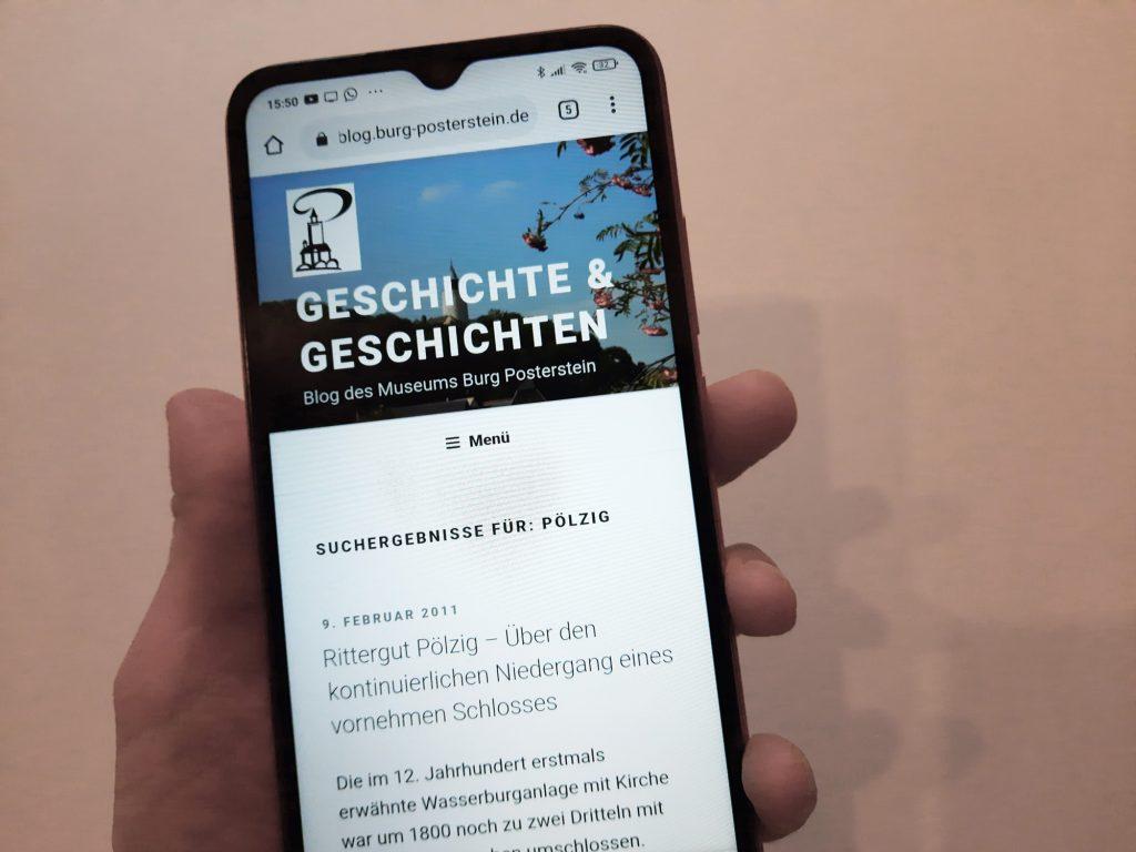 Hand hält Smartphone, auf dem der erste Blogpost des Blogs Geschichte und Geschichten des Museums Burg Posterstein geöffnet ist