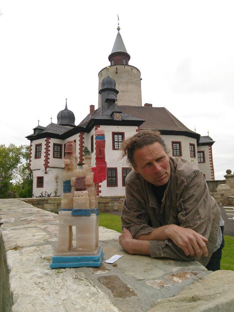 """Wolfgang Stöcker 2019 mit einem seiner Postersteiner """"Staubschreine"""" aus in Wachs gegossenem Staub aus der Burg Posterstein"""
